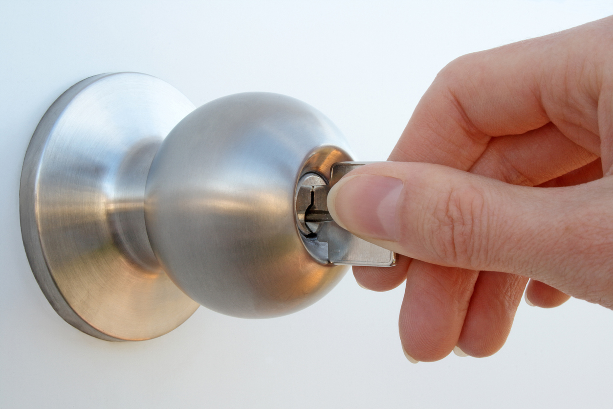 Woman's hand unlocking the door with a key.